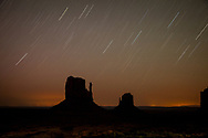 A long exposure captures star trails over the Mittens formations at Monument Valley, Arizona.