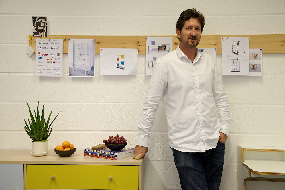 Leonhard Pfeifer, furniture designer, in his Hackney studio, London with the Abbeywood sideboard (left) manufactured in Estonia by Woodman and the Slope desk (right, it was awarded Design Guild Mark 2014) manufactured in Germany by Müller Möbelwerkstätten<br /> CREDIT: Vanessa Berberian for The Wall Street Journal<br /> GURU-Pfeifer