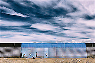 """Volunteers paint the border fence between the United States and Mexico to give it the illusion of transparency during her""""Borrando la Frontera"""" Art Project in Mexicali, Mexico April 9, 2016.  REUTERS/Sandy Huffaker   EDITORIAL USE ONLY"""