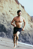 Shirtless man jogging on beach with rocky cliffs