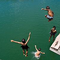 Four young kids jumping into Sangkhlaburi lake