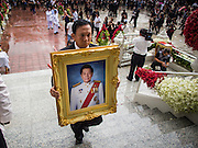 19 OCTOBER 2014 - BANG BUA THONG, NONTHABURI, THAILAND:  Apiwan Wiriyachai's portrait is carried into his cremation at Wat Bang Phai in Bang Bua Thong, a Bangkok suburb, Sunday. Apiwan was a prominent Red Shirt leader. He was member of the Pheu Thai Party of former Prime Minister Yingluck Shinawatra, and a member of the Thai parliament and served as Yingluck's Deputy Prime Minister. The military government that deposed the elected government in May, 2014, charged Apiwan with Lese Majeste for allegedly insulting the Thai Monarchy. Rather than face the charges, Apiwan fled Thailand to the Philippines. He died of a lung infection in the Philippines on Oct. 6. The military government gave his family permission to bring him back to Thailand for the funeral. His cremation was the largest Red Shirt gathering since the coup.    PHOTO BY JACK KURTZ