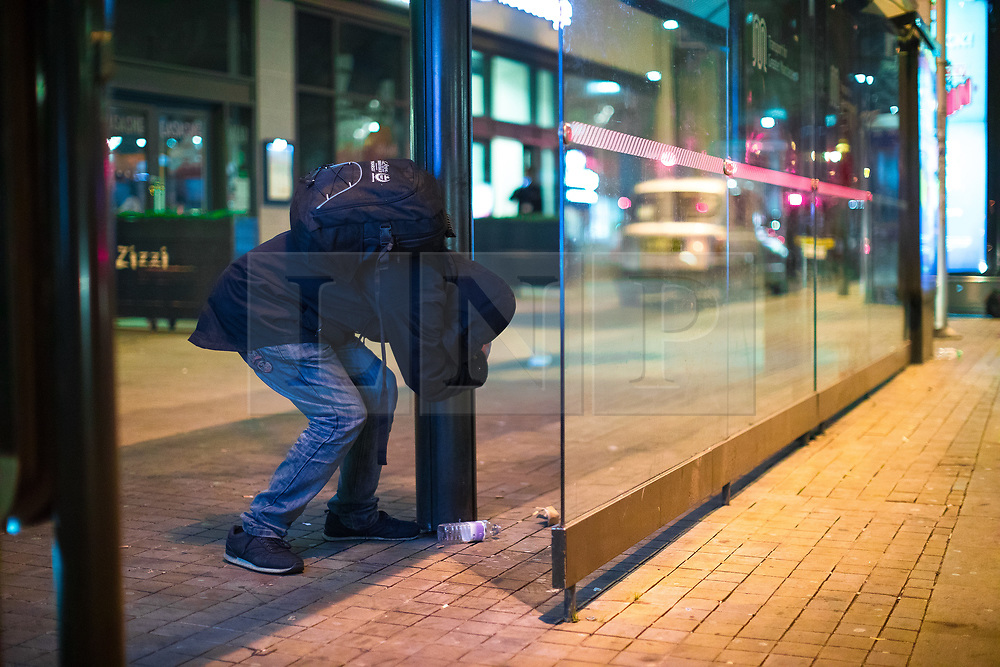 © Licensed to London News Pictures . 07/04/2017 . Manchester , UK . A man , believed to be suffering the effects of Spice , stands still bent over whilst gripping on a to a pole in the street for support , in Piccadilly . Greater Manchester Police have authorised dispersal powers and say they will ban people from the city centre for 48 hours , this evening (7th April 2017) , in order to tackle alcohol and spice abuse . Photo credit : Joel Goodman/LNP