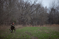 COYOTE HUNTER SETTING OUT HIS CALL AT THE EDGE OF AN OPEN FIELD