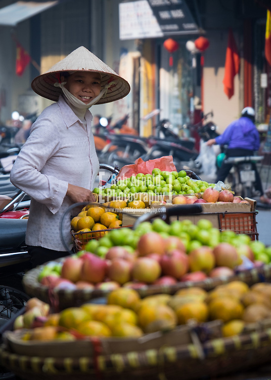 A street vendor selling fruit from the back of her bicycle in Hanoi's Old Quarter