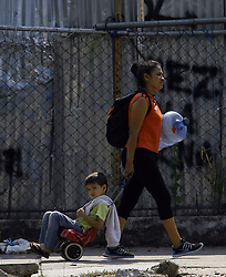 March 27, 2019 - Valencia, Carabobo, Venezuela - March 27, 2019.  A woman in search of drinking water, carries in her hand a container, while her son is moved in a makeshift vehicle, not receiving the vital liquid because of the failure in the pumping system  during the general blackout that affects a large part of the national territory.  In the city of Valencia, Carabobo state. Photo: Juan Carlos Hernandez (Credit Image: © Juan Carlos Hernandez/ZUMA Wire)