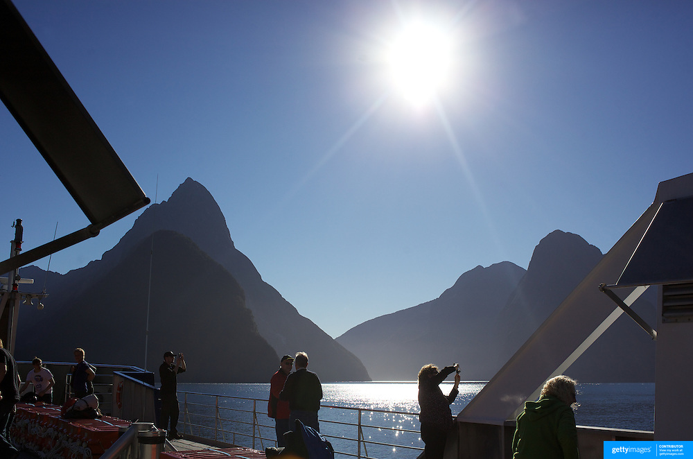 Tourists on a cruise ship on Milford Sound with Mitre Peak in the distance. .Milford Sound (Piopiotahi in Ma¯ori) is a fjord in the south west of New Zealand's South Island, within Fiordland National Park and the Te Wahipounamu World Heritage site. It has been judged the world's top travel destination and is acclaimed as New Zealand's most famous tourist destination..Milford Sound runs 15 kilometres inland from the Tasman Sea at Dale Point - the mouth of the fiord - and is surrounded by sheer rock faces that rise 1,200 metres (3,900 ft) or more on either side. Among the peaks are The Elephant at 1,517 metres (4,977 ft), said to resemble an elephant's head and The Lion, 1,302 metres (4,272 ft), in the shape of a crouching lion. Lush rain forests cling precariously to these cliffs, while seals, penguins, and dolphins frequent the waters and whales can be seen sometimes..Milford Sound sports two permanent waterfalls all year round, Lady Bowen Falls and Stirling Falls. After heavy rain many hundreds of temporary waterfalls can be seen running down the steep sided rock faces. .The beauty of this landscape draws thousands of visitors each day, with between 550,000 and 1 million visitors in total per year. This makes the sound one of New Zealand's most-visited tourist spots, and also the most famous New Zealand tourist destination.  Milford Sound, New Zealand. 29th April 2011. Photo Tim Clayton