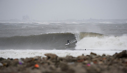 © Licensed to London News Pictures. 23/03/2013..Cleveland, England..Surfer Sandy Kerr from Tynemouth surfs the waves as the wintery weather continues to chill the country. Cleveland on the east coast of England suffered freezing cold temperatures and strong winds that brought big seas to the coastline...Photo credit : Ian Forsyth/LNP