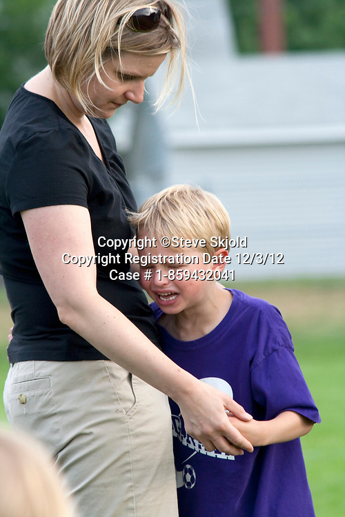Boy being comforted by mother after sports injury on soccer field. Carondelet Field by Expo School St Paul Minnesota MN USA