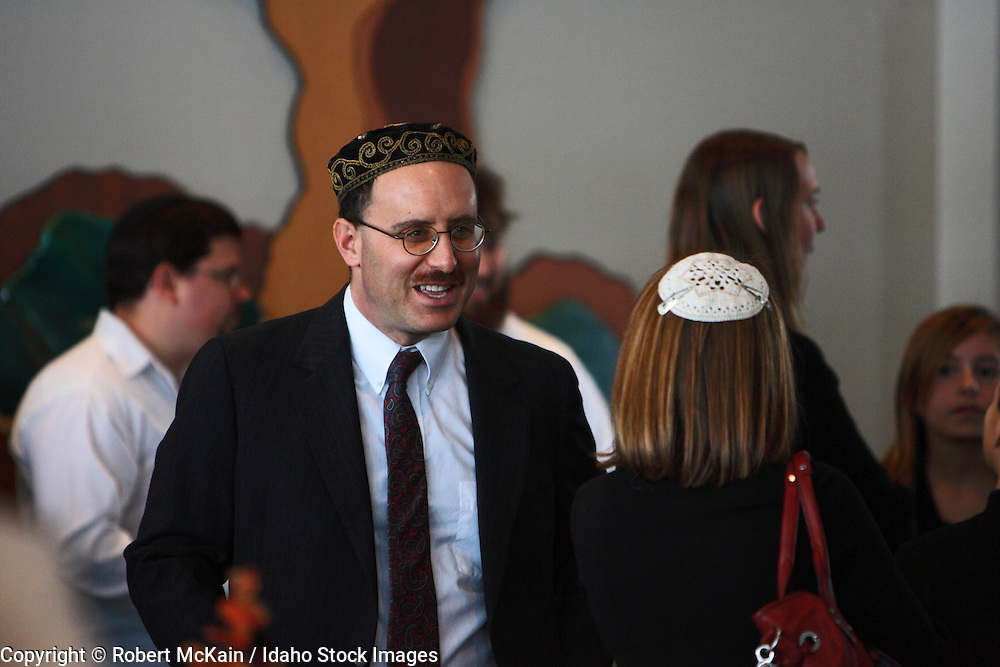 IDAHO. Boise. Jewish rabbi greeting guests at Bat Mitzvah celebration. December 2008. #pa080683  MR