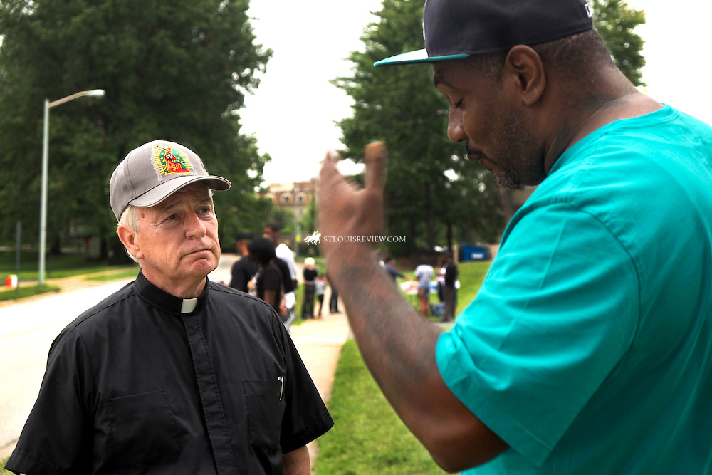 Msgr. Jack Schuler, left, spoke with Russell Robertson of Atlanta near the spot where Mike Brown was killed in Feguson. Robertson is a deacon at Grace Covenant Family Worship Center in Marietta, Ga.