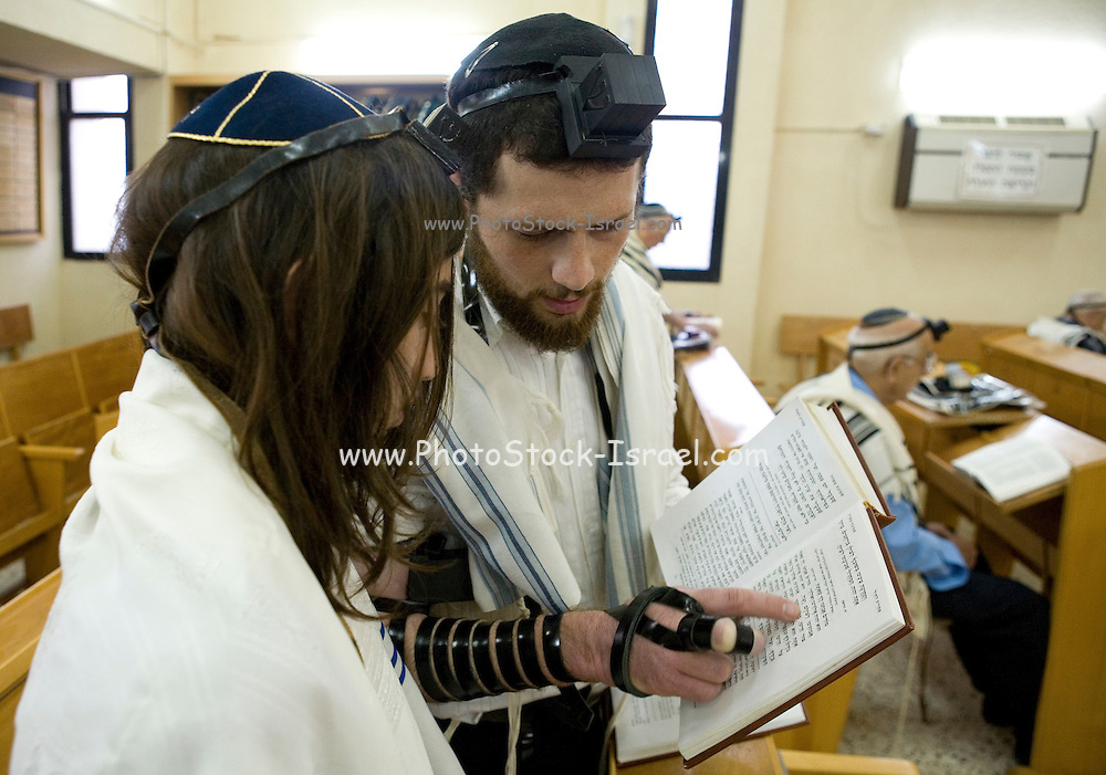 Bar Mitzvah ceremony in a synagogue Instructor teaching the service