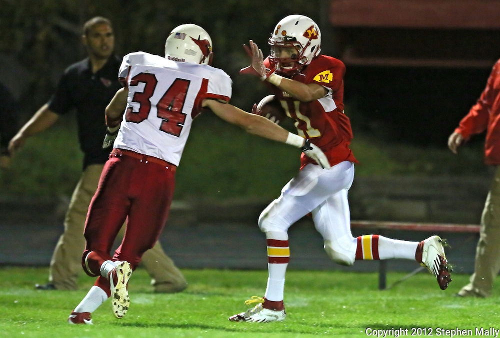Marion's Quinn Cannoy (11) tries to hold off Maquoketa's Alexander Gilmore (34) after a catch during the first half of the game between Maquoketa and Marion at Thomas Park Field in Marion on Friday, September 21, 2012.