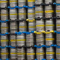 Metal beer barrels stacked in brewery yard