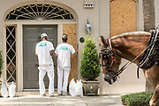 Workers secure plywood covering on a historic home as a horse carriage passes in preparation for Hurricane Irma September 8, 2017 in Charleston, South Carolina. Imra is expected to spare the Charleston area but hurricane preparations continue as Irma leaves a path of destruction across the Caribbean.