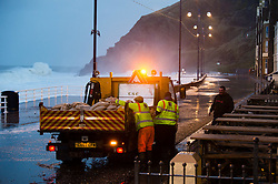 © London News Pictures. Aberystwyth, Wales. 03/01/2014. Council workers laying sand bags. A 5.6m high springtide and gale force south westerly winds bring  massive weaves pounding against the promenade and harbour at Aberystwyth on the west wales  coast.  The entire promenade was  closed to traffic because of fears for safety. Over 20 severe warnings have been issued for flooding in England and Wales, with the weather set to worsen over the next 24 hours, Across much off the south and west coast. Photo credit: Keith Morris/LNP
