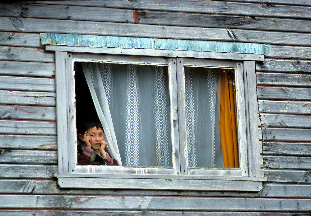 A young boy sits pondering his life at a weathered window in Calbulco, Puerto Montt area, Chile.