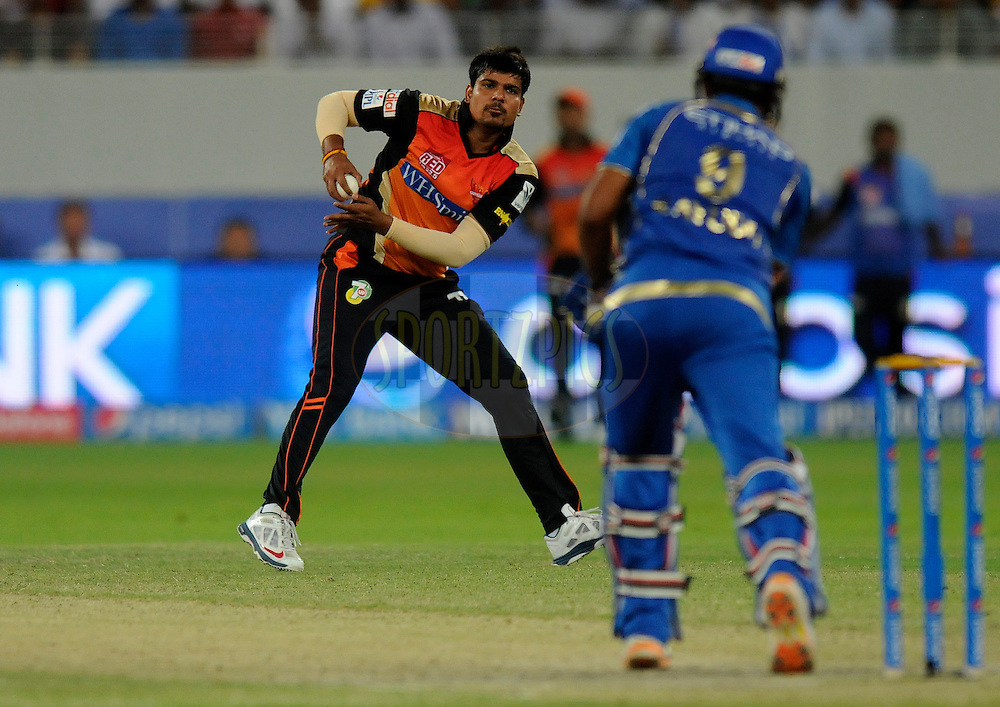 Karn Sharma of the Sunrisers Hyderabad fields of his own bowling during match 20 of the Pepsi Indian Premier League Season 2014 between the Mumbai Indians and the Sunrisers Hyderabad held at the Dubai International Stadium, Dubai, United Arab Emirates on the 30th April 2014<br /> <br /> Photo by Pal Pillia / IPL / SPORTZPICS