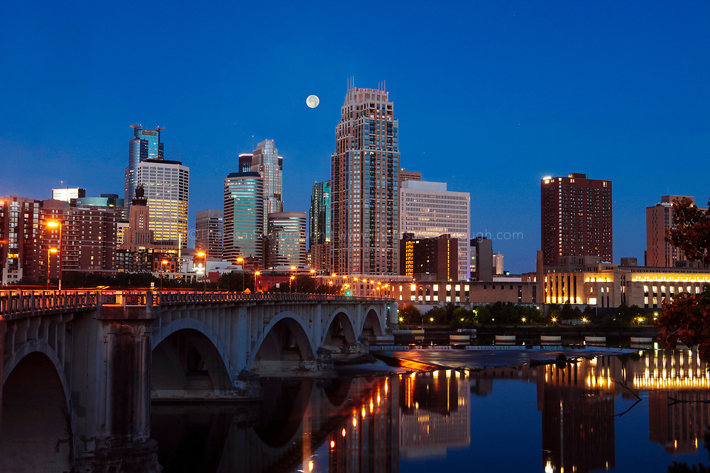 Minneapolis Minnesota skyline in the early morning with the full moon. Near the Third Street bridge over the Mississippi River.