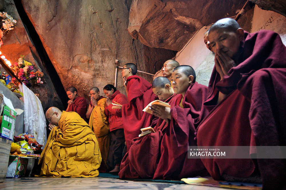 Buddhist Nuns praying with a monk in the cave of Guru Padmasambhava in Rewalsar, Mandi, Himachal Pradesh, India