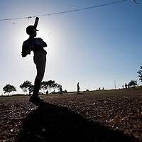Dominican Republic, La Romana, Silhouette of batter warming up in on-deck circle during community baseball game