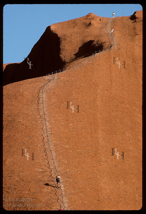 Tourists struggle up and down Ayers Rock using chain on section Aborigines see as a mala's back. Australia