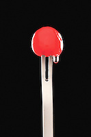Single cocktail cherry in fork black background