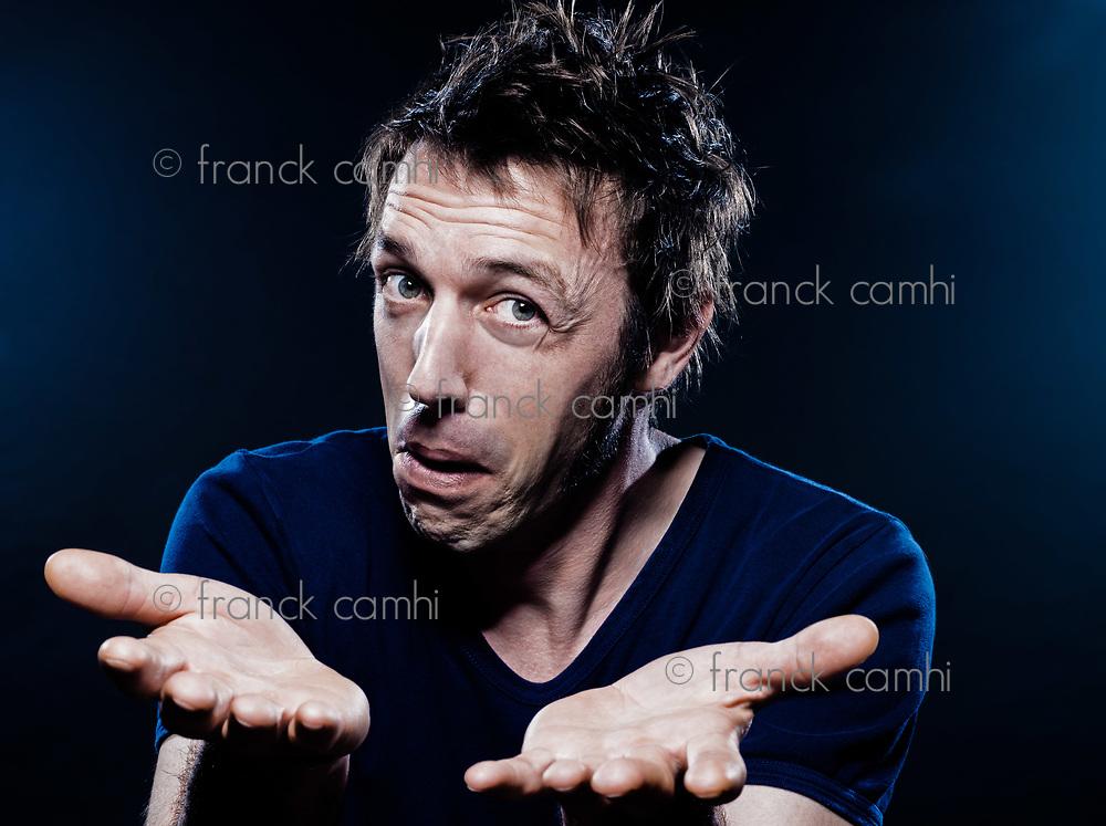 studio portrait on black background of a funny expressive caucasian man hesitant puckering