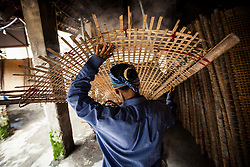 A Vietnamese woman carries a bamboo drying rack over her head in Cu Da Village, Hanoi, Vietnam, Southeast Asia