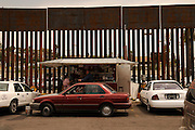 Patrons purchase food from a food stand in Nogales, Sonora, Mexico, located along the border wall at Nogales, Arizona, USA.