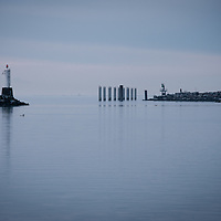 Soft muted colours of winter sunset over lighthouse and jetty.