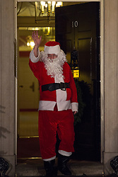 © licensed to London News Pictures. London, UK 17/12/2012. A 'Santa' walking out from Number 10 after the Downing Street Christmas Party. Photo credit: Tolga Akmen/LNP