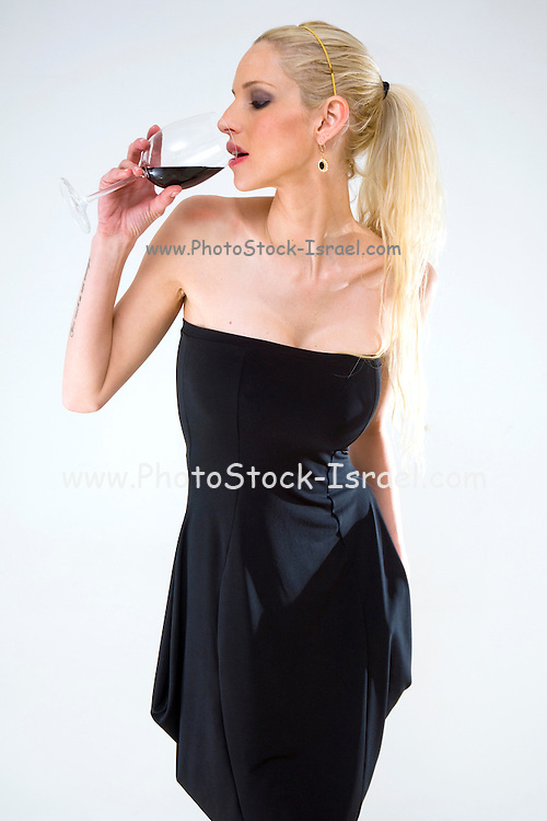 Young female Blond model mid twenties with a black evening dress drinking red wine on white background