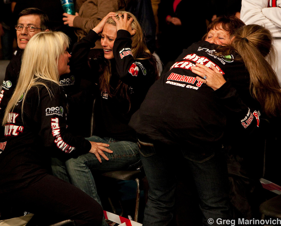 Mikey Schultz wife (seated left, long blonde hair) holds her head is desapair as his mother (right, seated) is comforted by family and friends at  Wembley sports arena, Johannesburg south, Nov 20, 2009, South Africa after self confessed hired killer in the Brett Kebble murder case Mikey Shultz was knocked out by Zimbabwean Tineyi Maridzo in the first round of the all WBO Africa title fight in Johannesburg Friday night. Photo Greg Marinovich