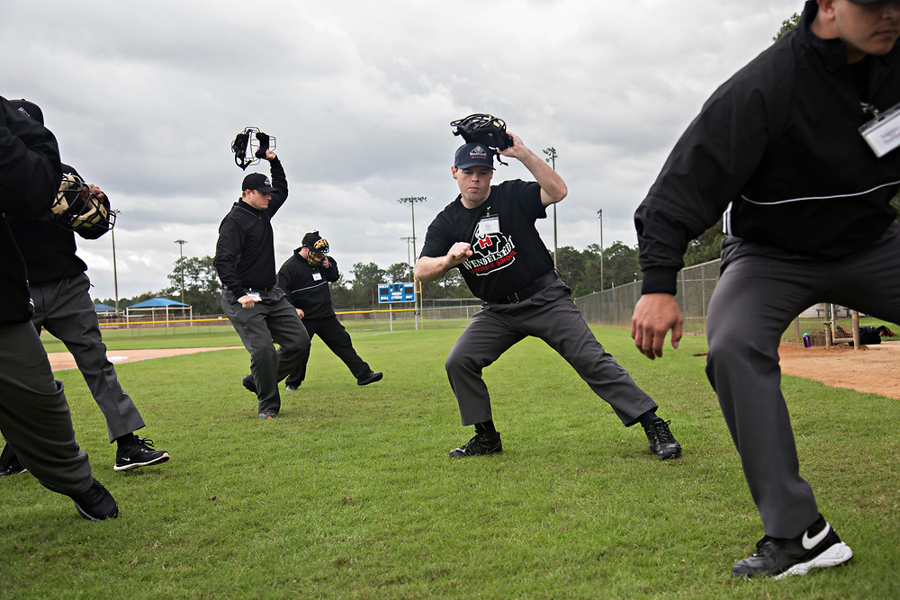 DAYTONA BEACH, FL - JANUARY 5, 2016: Eric Swift of Kalispell, Montana, second from right, works on the motion of dropping back and taking off his mask during Umpire School. (Photo by Melissa Lyttle)