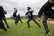 Eric Swift of Kalispell, Montana, second from right, works on the motion of dropping back and taking off his mask during Umpire School.
