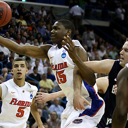 Mar 24, 2011; New Orleans, LA; Brigham Young Cougars forward Logan Magnusson (12) hooks the arm of Florida Gators forward Will Yeguete (15) drawing a foul during the first half of the semifinals of the southeast regional of the 2011 NCAA men's basketball tournament at New Orleans Arena.  Mandatory Credit: Derick E. Hingle