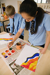 Secondary school students painting pictures in an art lesson,