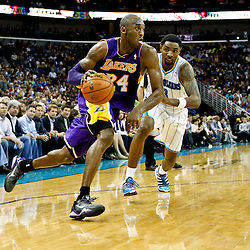 Dec 5, 2012; New Orleans, LA, USA; Los Angeles Lakers shooting guard Kobe Bryant (24) drives past New Orleans Hornets shooting guard Roger Mason Jr. (8) during the second quarter of a game at the New Orleans Arena.  Mandatory Credit: Derick E. Hingle-USA TODAY Sports
