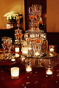 Wedding champagne glass tower resting on a mirror base with candles at The Century House, Latham, NY