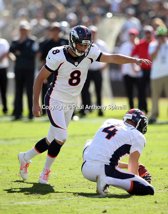 Denver Broncos punter Britton Colquitt (4) holds as Denver Broncos kicker Brandon McManus (8) kicks a third quarter field goal that cuts the Oakland Raiders lead to 7-6 during the 2015 NFL week 5 regular season football game against the Oakland Raiders on Sunday, Oct. 11, 2015 in Oakland, Calif. The Broncos won the game 16-10. (©Paul Anthony Spinelli)