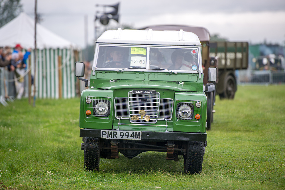 Front view of vintage green Land Rover being driven along in the grass, Masham, North Yorkshire, UK