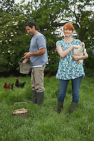 Couple feeding hens in garden portrait