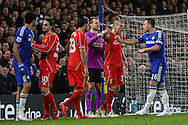 John Terry of Chelsea (right) pushes back Martin Skrtel of Liverpool (2nd right) after he'd put his head against Diego Costa's head (left) during the Capital One Cup Semi Final 2nd Leg match between Chelsea and Liverpool at Stamford Bridge, London, England on 27 January 2015. Photo by David Horn.