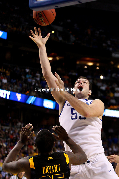Mar 19, 2011; Tampa, FL, USA; Kentucky Wildcats forward Josh Harrellson (55) shoots over West Virginia Mountaineers guard Darryl Bryant (25) during the second half of the third round of the 2011 NCAA men's basketball tournament at the St. Pete Times Forum. Kentucky defeated West Virginia 71-64.  Mandatory Credit: Derick E. Hingle