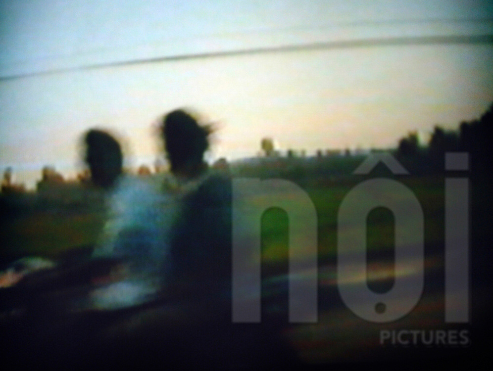 Very oniric picture of two men driving fast a motorbike in countryside of Vientiane, Laos, Asia. Picture is blurred and motion feeling is strong.