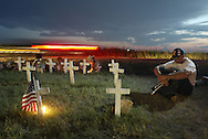 At Camp Casey II during the Cindy Sheehan Vigil, Jeff Key, right, who serves with the Marines in Iraq, sits near the cross representing a Marine from his company who died in Iraq.