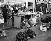 Moore Street, Dublin.      (J97)..1975..23.12.1975..12.23.1975..23rd December 1975..For well over a hundred years Moore Street has served the citizens of Dublin. The longest running open air fruit and vegatable market offers value for money,particularly to those where money is in short supply. Predominately a fruit and veg market there are several traders who sell fish and seasonal goods, as illustrated by the photographs showing turkeys and holly wreaths being sold on the run up to Christmas..A well earned rest, this young man grabs a cup of tea and a bite to eat during a lull in the activity.