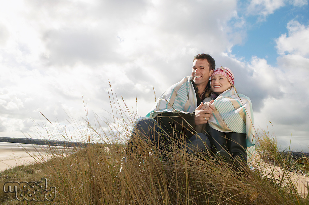 Couple wrapped in blanket embracing at ocean