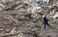 A rescue worker balances in the mud as he looks for victims in the mudslide near Oso, Washington as efforts continued to find victims March 26, 2014. The death toll from a massive landslide in Washington state stood at 24 on Wednesday, but the mud-stricken community braced for a higher body count as search teams combed through debris looking for scores of people still missing four days after the disaster. REUTERS/Rick Wilking(UNITED STATES)